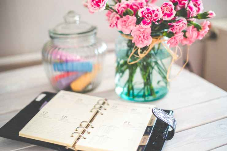 personal organizer and pink flowers on desk