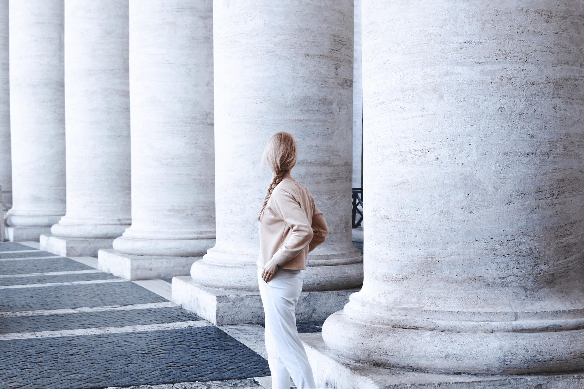 photo of woman standing beside concrete pillar
